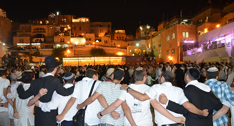 men singing and dancing during Sukkot
