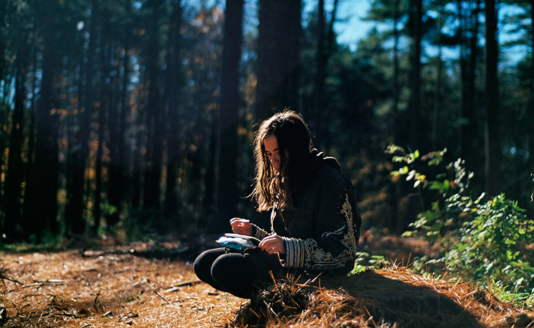 Girl sitting on the ground in a forest writing in a journal