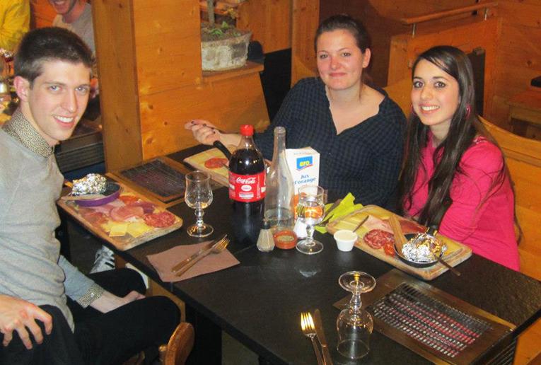 Friends making raclette in France