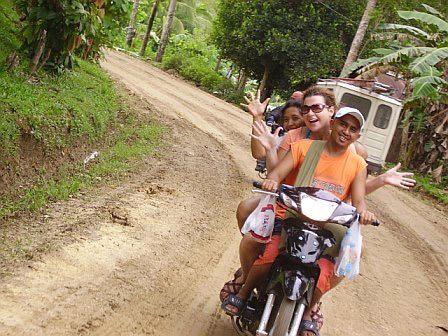 A woman riding a motrobike.