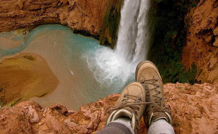hiking boots on a cliffside looking out on a waterfall and pool below