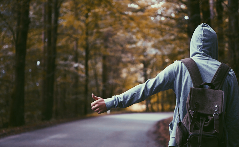 man with a backpack hitchhiking