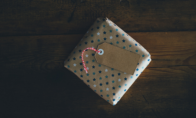 Small wrapped gift with blue and white stars on the wrapping paper
