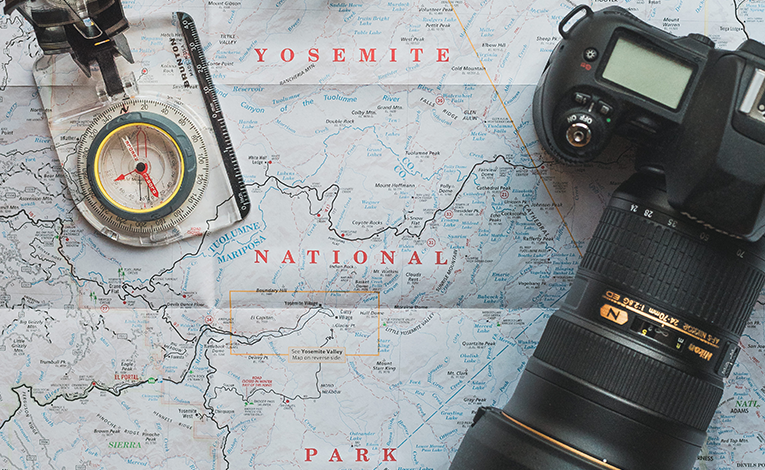 map of yosemite national park with a compass and DSLR with a telephoto lens