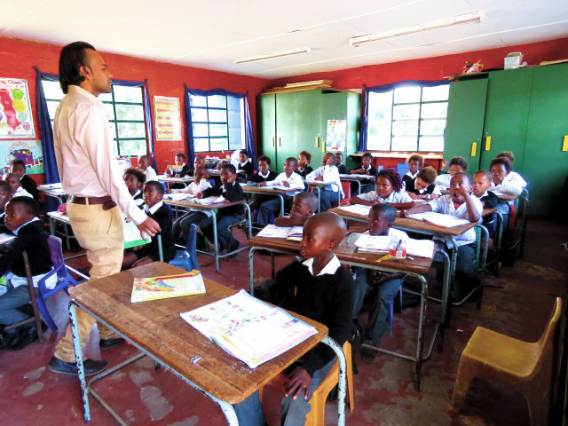 Volunteer teacher standing in front of his class in South Africa