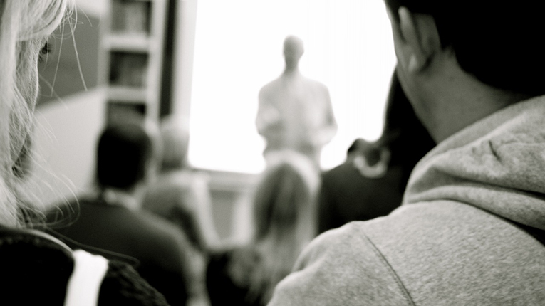 Black and white view of a teacher presenting to his class