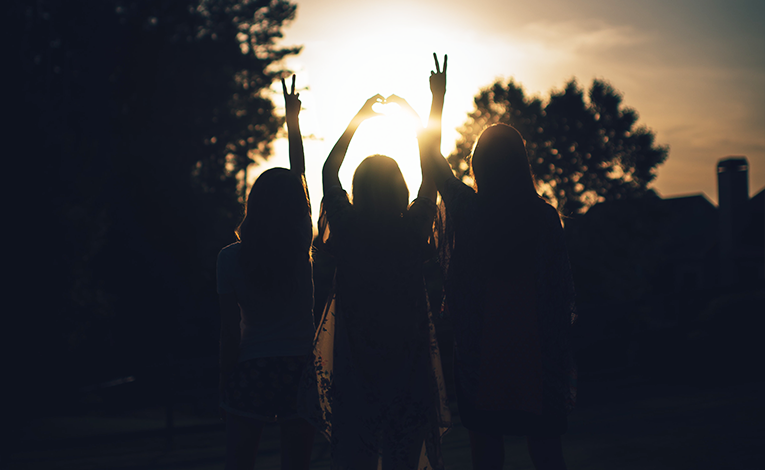 Three friends in the sunset raising their arms in the air