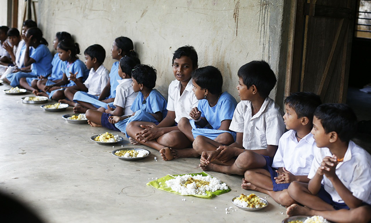 Children eating meals in a school in India