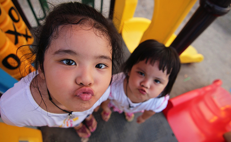 Two young Thai girls making silly faces