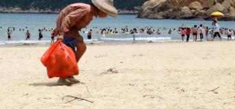A woman looking for recyclable materials to exchange for money on a perfect day at the beach.