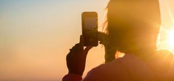 Girl taking a photo of a sunrise