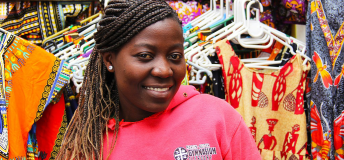 African woman standing in front of her store