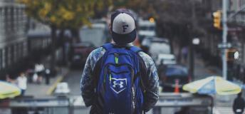 young man with backpack facing busy city street
