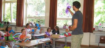 Volunteer teacher teaching a lesson to elementary students