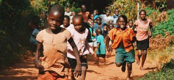 Small Rwandan children running and smiling