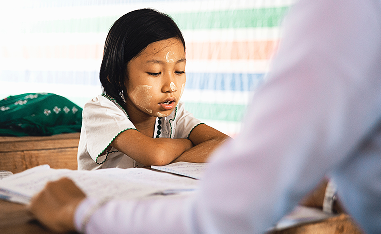 Young girl studying with teacher