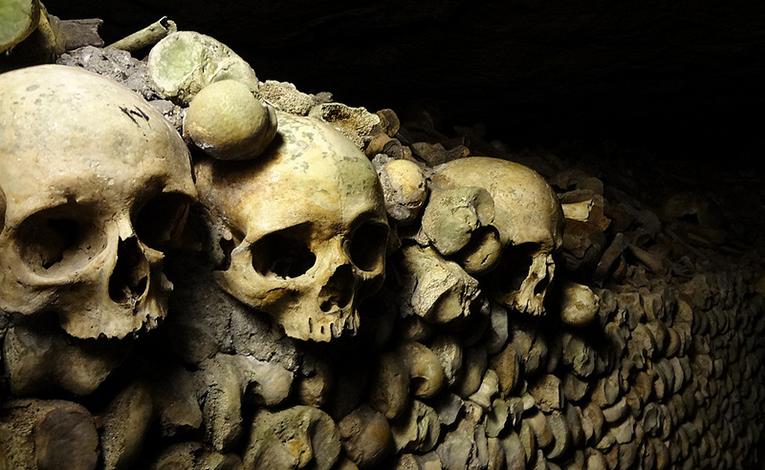 Catacomb corridors lined with skulls and bones
