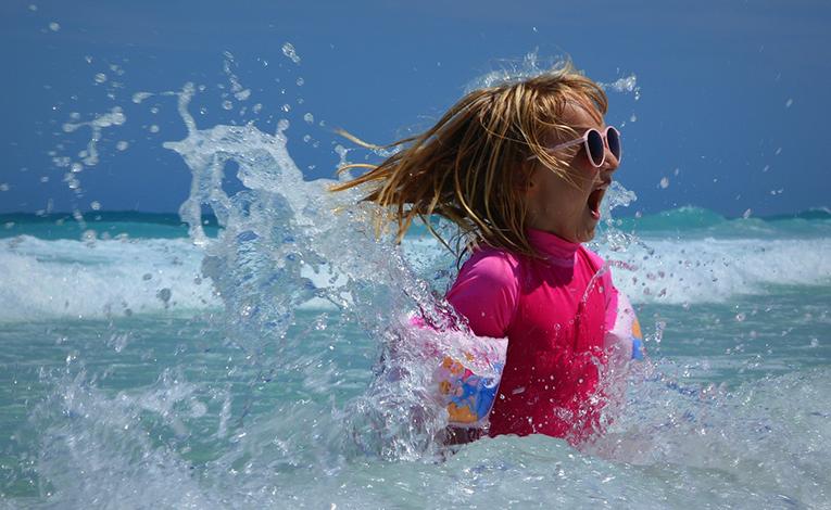 little girl splashing in waves