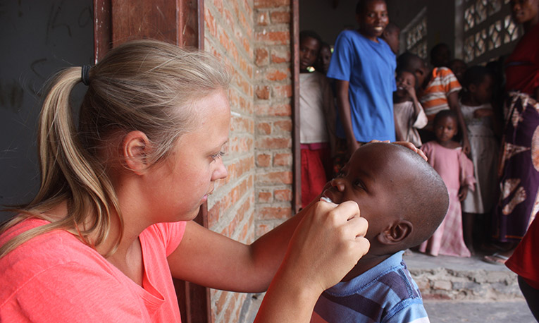 Volunteer in Malawi giving a child a dental check up