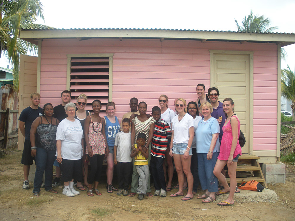 Students from Saint Xavier University in Chicago stand in front of a house that they built in Belize along with the family who will be living in it.