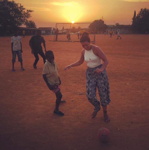 Volunteer playing soccer with kids in Ghana