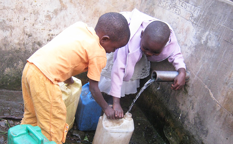Children getting water from an open faucet