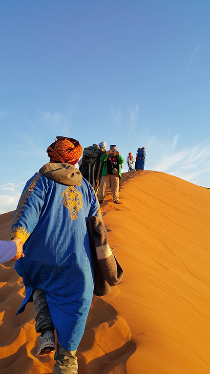 People trekking through the desert in Morocco