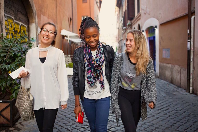 Students walking down a cobblestone street in Rome, Italy